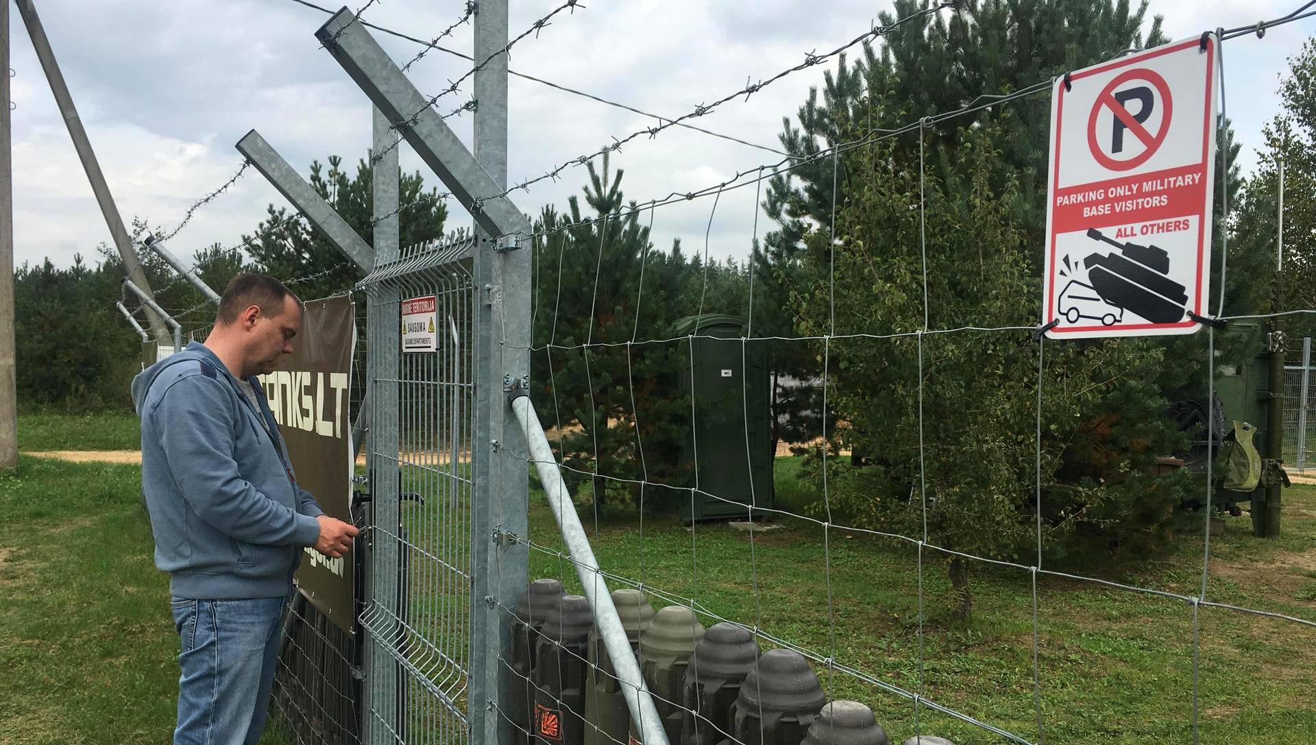 Zilvinas Pastarnokas avaa Defence Projects -yrityksen taisteluharjoitusalueen porttia. Paljonpuhuva kyltti varoittaa sivullisia siitä, että alueen lähistölle ei kannata edes parkkeerata.