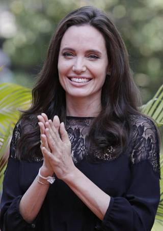 Jolie edusti iloisena tyylikkääseen kokomustaan asuun pukeutuneena.