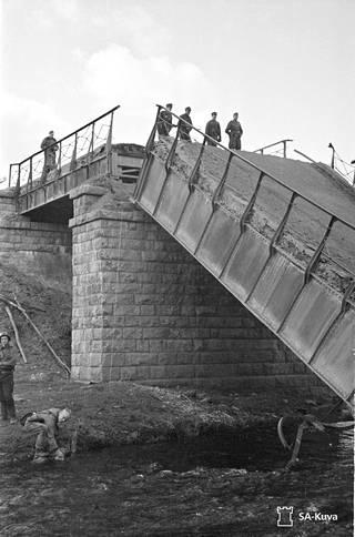 Rajajoen yli Mainilassa kulkeva silta räjäytettiin jatkosodassa. Suomalaisia sotilaita ylittämässä jokea hyökkäyksen edettyä Mainilaan.
