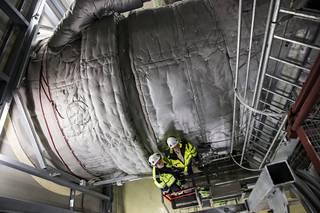 Laitosvastuuhenkilö Pekka Anttila ja kunnossapitopäällikkö Harri Ollikainen näyttävät häviävän 220000 hevosvoimaa tuottavan kaasuturbiin lämpösuojien sekaan. Vanhempia häiriöreservivoimaloita pyörittävät Draken-hävittäjien Rolls&Royce Avon-moottoreista kehitetyt turbiinit.