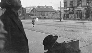 Tulitus on tauonnut, ja punaisten antautuminen Siltasaaressa alkaa. Punakaartilainen lähestyy saksalaisia valkoisen lipun alla.