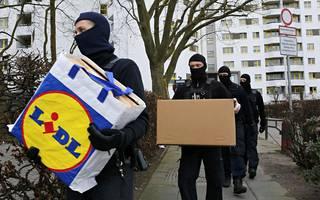 Poliisi kantoi takavarikoitua materiaalia ulos asuintalosta.
