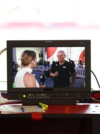 Tuomas Raja näkyi Ylen selostuspisteellä olevan monitorin ruudusta, kun hän oli stadionin ulkopuolella ennakoimassa alkavaa yleisurheiluiltaa Laura Arffmanin kanssa.