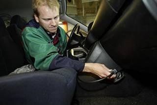 Katsastusaseman päällikkö Janne Koskelainen tekee autoon pakokaasutestiä ja kytkee testilaitteiston kiinni testattavan ajoneuvon OBD-väylään. Kuva vuodelta 2004.