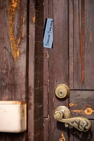 Motelli On Linen ovi on korjattu pikaisesti laudanpätkällä. Ovenkarmeissa on poliisin logolla varustettuja lätkiä.