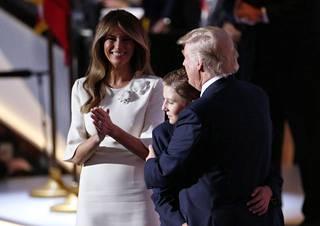 Donald Trump (vas.) poikansa Barronin (kesk.) ja vaimonsa Melanian kanssa.