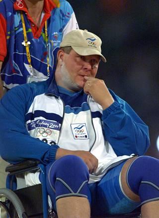 Loukkaantunut Timo Aaltonen kuljetettiin Sydneyn olympiakisojen kuulapaikalta pyörätuolilla syksyllä 2000.