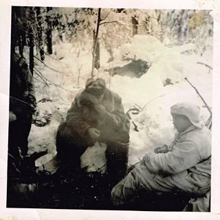 Vääpeli Boris Hohlogorski taukonuotiolla vangitsijoidensa kanssa.
