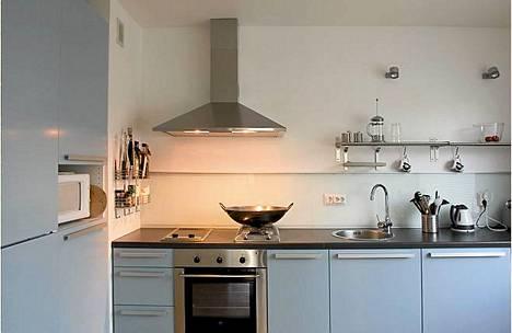 Ilman yläkaappeja keittiö on avarampi. Avohyllyille voi kätevästi ripustaa keittiötarvikkeita. Työtason takana on opaalilasi, joka on kevyt ja käytännöllinen vaihtoehto kaakelille.