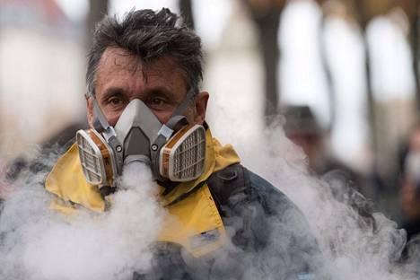 """Mies tupakoi kaasunaamarissaan Nantesissa, jossa myös järjestettiin keltaliivien """"juhlamielenosoitus""""."""