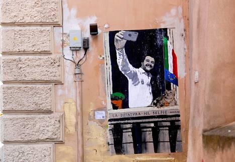 """Maalaus Salvinista ottamassa selfietä Benito Mussolinin kanssa. Kuva otettu toukokuussa 2019 Roomassa. Tekstissä lukee: """"Selfien diktatuuri."""""""