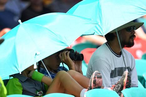 Krikettiottelun katsojat suojautuivat auringolta ja helteeltä Sydneyssä sunnuntaina.