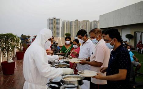 Sairaalahenkilökunta tarjoilee ruokaa koronaviruspotilaille New Delhin lähistöllä sijaitsevassa sairaalassa.