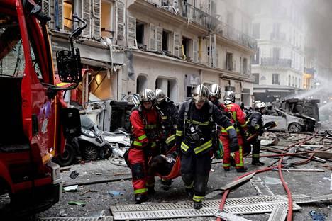 Palomiehet evakuoivat räjähdyksessä haavoittuneita ihmisiä.