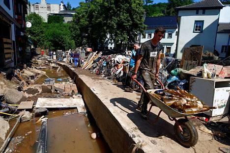Mies siivosi tulvatuhoja kuljettamalla lasipulloja kottikärryssä.
