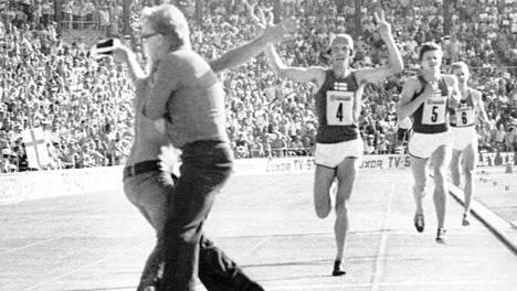 Suomi tulee maaliin kolmosvoittajana. Pekka Päivärinta edellä, Ismo Tuokonen toisena ja Martti Vainio kolmantena. Paidaton katsoja painii järjestysmiehen kanssa.