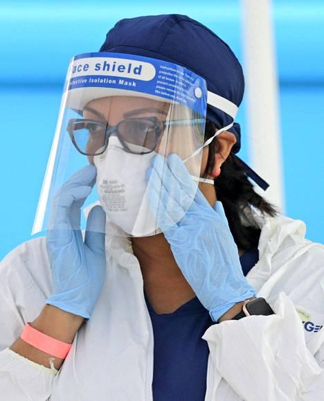 Terveydenhoitoammattilainen käyttää sekä kasvovisiiriä että hengityssuojainta Miamissa, Yhdysvalloissa.