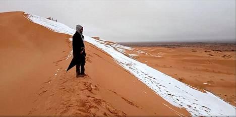 Mies ihmetteli Saharalle satanutta lunta Algeriassa.