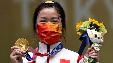 Kiinalainen Yang Qian voitti Tokion olympialaisten ensimmäisen kultamitalin. Hän riemuitsi palkintokorokkeella maski kasvoillaan.