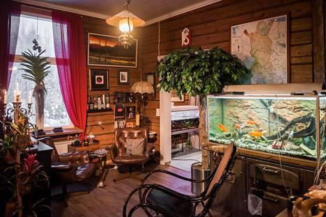 """""""Sikarihuone"""" on pyhitetty leppoisaan oleiluun. Sen viereisen olohuoneen puolelta löytyvät muun muassa lattiasta kattoon ulottuva kirjahylly sekä aiemmin Ehrnroothien sukukartanossa käytössä ollut jalopuinen työpöytä."""