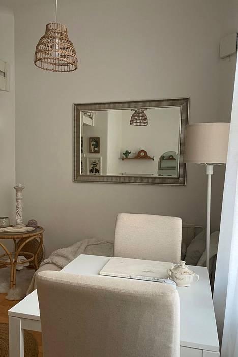 Nukkaan sijoitettu divaani toimii sohvana. Asuntoon mahtuu myös pieni ruokapöytä tuoleineen.