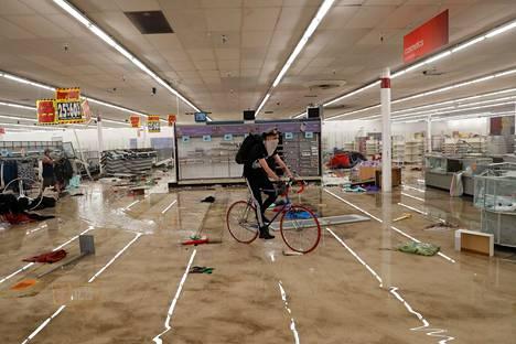 Mies pyöräilee mellakoitsijoiden vahingoittaman liikkeen sisällä Minneapolisissa.