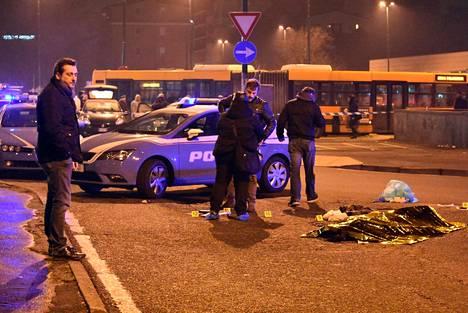 Amrin peitelty ruumis ampumisen jälkeen poliisiauton vierellä.