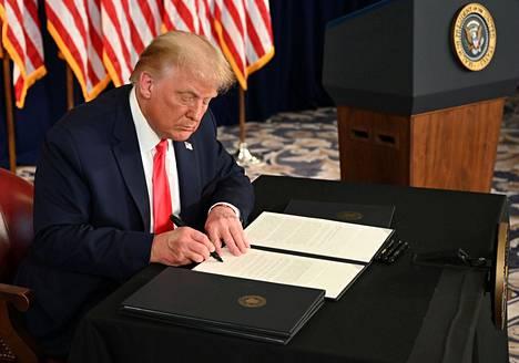 Donald Trump allekirjoittamassa asetusta lauantaina.