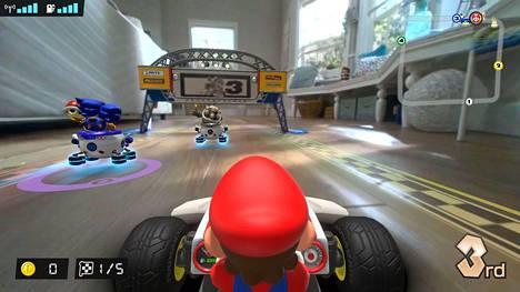 Mario Kart Live: Home Circuit sekoittaa hupaisasti tosimaailman ja videopelin. Ruudulta näkee, kuinka lattialla kurvaileva leluauto osallistuu samaan aikaan pelin sisällä kiihkeään kilpa-ajoon.