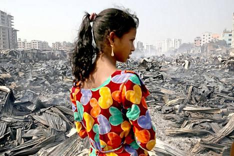 Slummien tyhjätaskut. Bangladeshilaistyttö tarkasteli slummipalon tuhoja Dhakassa keskiviikkona.