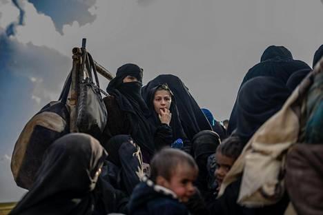 Naisia ja lapsia kuorma-auton kyydissä matkalla pois Baghuzista.