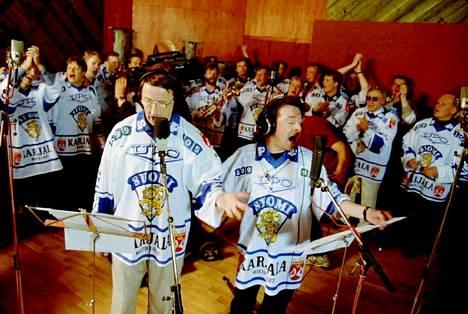 Curt Lindström ja Kirka valmistautumassa levytykseen Leijonajoukon elämöidessä taustalla Tampereella vuonna 1995. Maailmanmestarit levyttävät Den glider in -kappaleen yhdessä Kirkan kanssa.