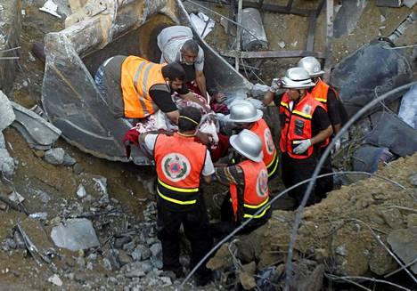 Pelastustyöntekijät etsivät raunioista ruumiita.