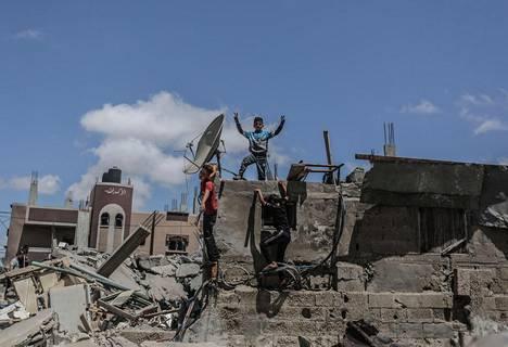 Lapset kiipeilivät tuhoutuneen talon raunioilla maanantaina Gazassa.