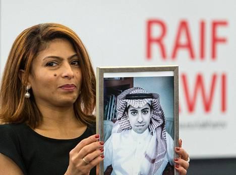 Raif Badawin vaimo Ensaf Haidar pitää miehensä kuvaa. Haidar asuu pariskunnan lasten kanssa maanpaossa Kanadassa.