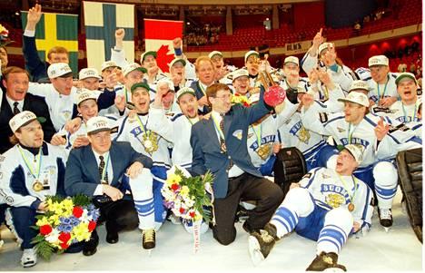 Suomen joukkue juhlii. Taustalla mitalikolmikon liput: kultaa Suomi, hopeaa Ruotsi, pronssia Kanada.