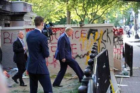 Presidentti ohitti mielenosoittajien tekemät graffitit.