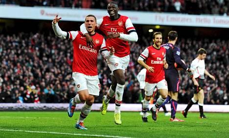 Lukas Podolski ja Yaya Sanogo juhlivat Arsenalin voittomaalia ja jatkopaikkaa Cupissa.