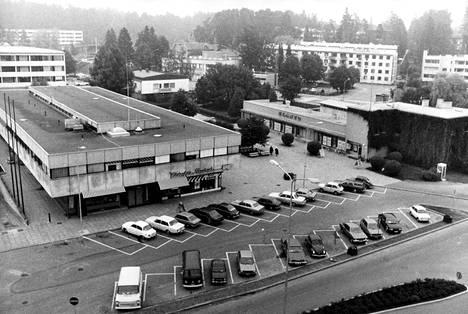 Kauniaisten keskusta vuonna 1979. 1980-luvulla Kauniaisissa nousi tyytymättömyys keskusta-aluetta kohtaan. Muun muassa liikennejärjestelyjen sekavuus ja pysäköintipaikkojen puute harmittivat asukkaita.