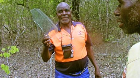 Kylän päällikkö Jonas Mupange näyttää löytämäänsä ohjaamon lasipalaa.