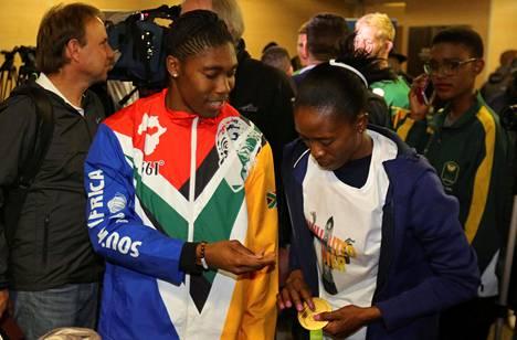 Caster Semenya antoi Rion kultamitalinsa vaimolleen Violet Raseboyalle Johannesburgin lentokentällä.