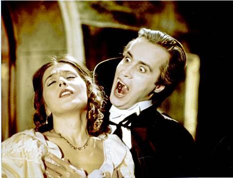Kreivi Dracula (Dolivo) iskemässä hampaansa laulajatar Sylva Dietrichin (Maija Lokka) kaulaan Kivikasvojen vampyyrioperetissa Lepakkolinna vuonna 1980.