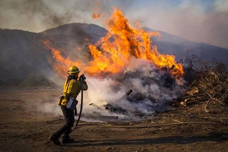 Palomies yrittää hillitä liekkien leviämistä Etelä-Kaliforniassa.