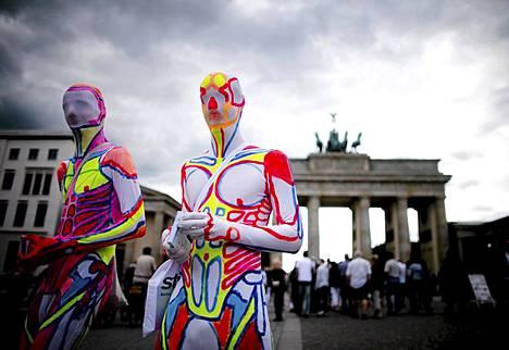 Liikkuvat taideteokset. Kaksi taidepukuihin sonnustautunutta henkilöä jakaa postikortteja Berliinin kuuluisan maamerkin Brandenburgin portin edessä Saksassa. Asut on suunnitellut taiteilija Anna Jordan, joka pyrkii herättämään huomiota teoksillaan.