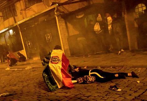 Mielenosoittaja auttaa kaveriaan La Pazissa Boliviassa.