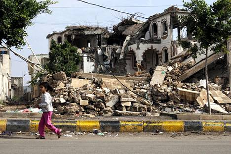 Jemeniläistyttö käveli ilmaiskulla tuhotun talon ohitse Jemenin Sanaassa elokuun alussa.