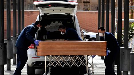 Hautaustoimiston työntekijät, jotka pitivät hengityssuojaimia, asettivat arkkua ruumisautoon Mardridissa, Espanjassa, tiistaina.