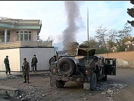 Afgaanisotilaat vartioivat aluetta. Taustalla nousi savua palavasta YK:n vierastalosta.