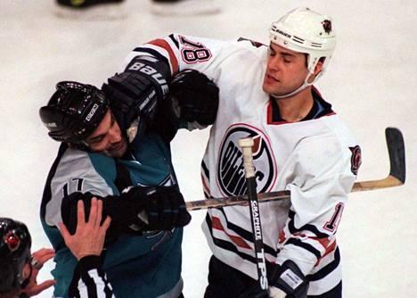 Joe Muprhy (vas.) edusti vuosina 1997–1999 San Jose Sharksia. Kuvassa Murphy ottaa yhteen Edmonton Oilersin Ethan Moreaun kanssa maaliskuussa 1999 pelatussa ottelussa.