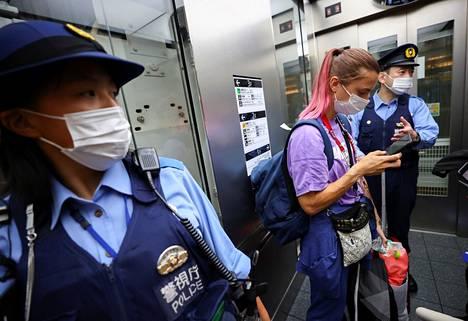 Krystsina Tsimanouskaja poliisien seurassa Hanedan lentokentällä Tokiossa sunnuntaina.